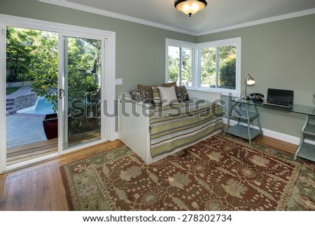 Stylish living room with home office, modern chair, desk, closet and couch bed with sliding doors leading to outdoors. - stock photo