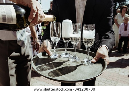stylish luxury amazing champagne and pouring glasses on a tray, for the celebration of a wedding, catering holiday in the restaurant - stock photo