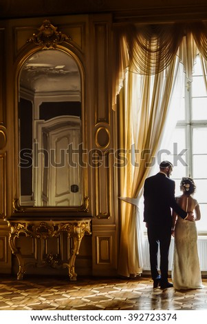 stylish luxury bride and handsome elegant groom posing in light at gorgeous window on the background of rich interior in old building - stock photo