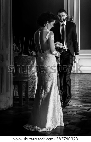 stylish luxury bride and handsome elegant groom posing on the background of rich interior in old building