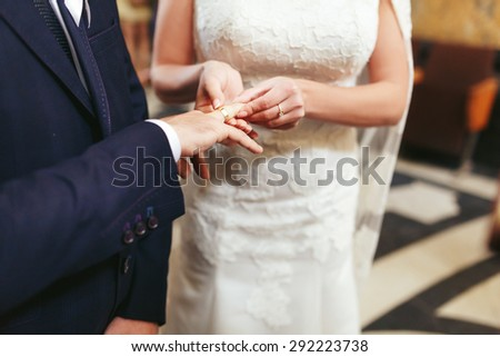 stylish luxury red haired bride and elegant groom, puts on a ring, wedding ceremony in the old church