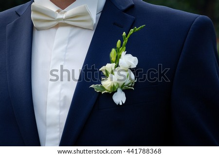 stylish luxury young cute Groom in blue suit with white bow tie and white flowers
