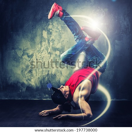 Stylish man dancer showing break-dancing moves with magic beams around him  - stock photo