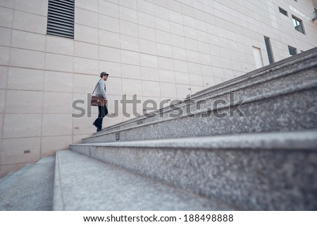 Stylish man going up the stairs, view from the side - stock photo