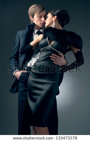 Stylish man in a suit and a girl in an evening black dress - stock photo