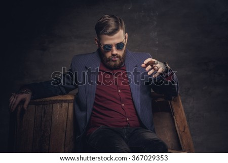 Stylish man in a suit smoking cigar.