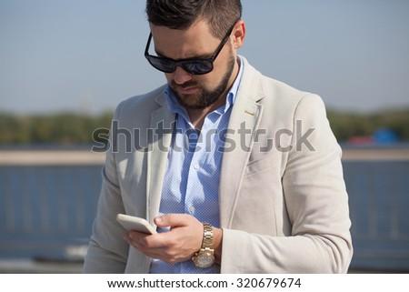 stylish man in business attire using phone - stock photo