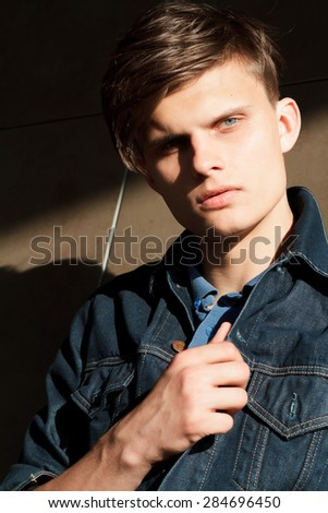 Stylish man in denim jacket standing near wall of building