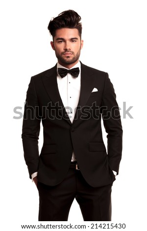 stylish man in elegant black suit and bowtie standing with hands in pockets on white background - stock photo