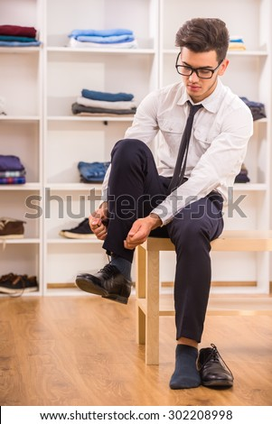 Stylish man in glasses tying shoe laces while sitting on chair at the dressing room. - stock photo