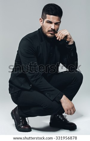 stylish man sitting in black suit and boots in studio
