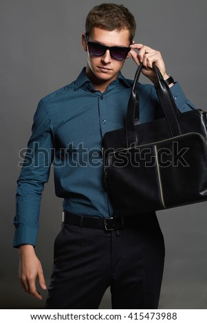 stylish man with a handbag. Handsome man in sunglasses