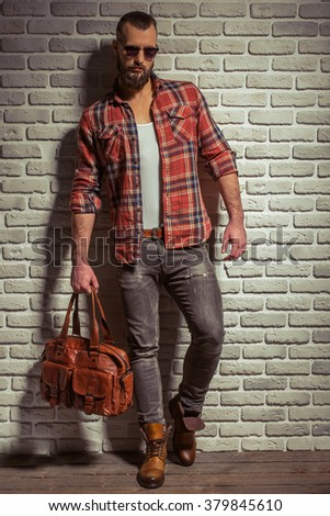 Stylish man with beard in casual shirt and sunglasses holding a brown leather bag, standing against brick wall - stock photo