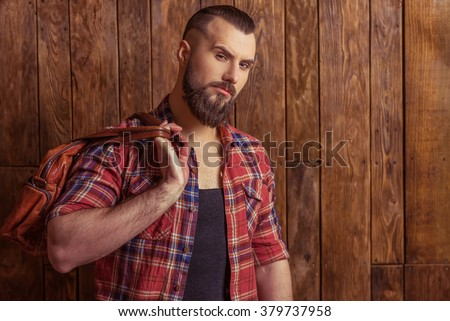 Stylish man with beard in casual shirt holding a brown leather bag and looking at camera, standing on a wooden background - stock photo