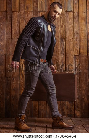 Stylish man with beard in leather jacket holding a suitcase and looking at camera, standing on a wooden background