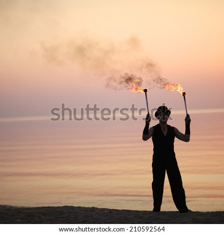 Stylish man with pair of burning juggling torches on the beach - stock photo