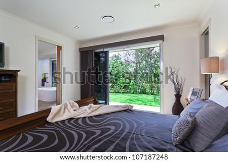 Stylish master bedroom in luxury Australian mansion - stock photo