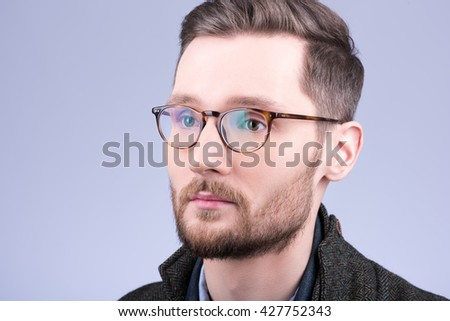 Stylish men's glasses. Closeup portrait of young man with beard and mustache. Neutral grey background