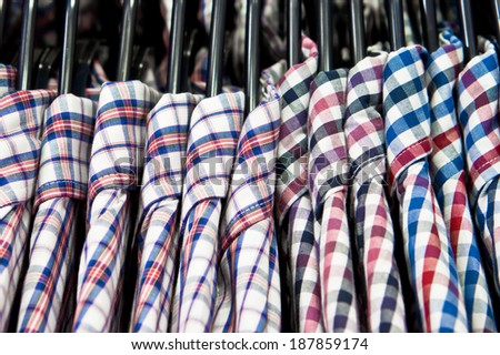 Stylish men's shirts hanging in a store