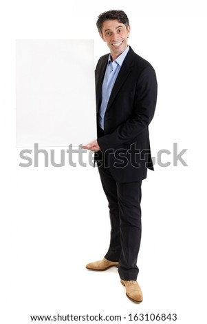Stylish middle aged businessman or salesman with a cheesy friendly grin standing holding a blank white board for your text or advertisement, isolated on white