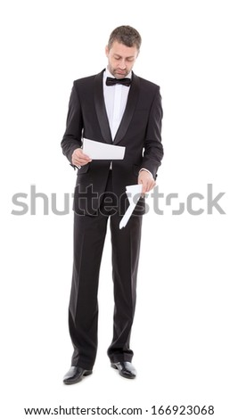 Stylish middle-aged man in a bow tie and tuxedo reading the document in his hand