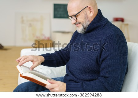 Stylish middle-aged man relaxing at home sitting on a sofa with a good book reading with a smile of enjoyment, side view - stock photo