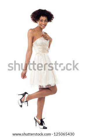 Stylish model in stilettos posing sideways with raised leg, white background.