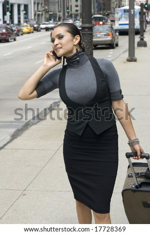 Stylish model looking for taxicabs downtown on a sunny day - stock photo