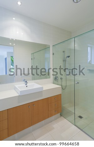 Stylish modern bathroom with shower, sink and mirror