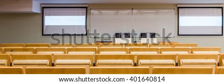 Stylish modern classroom in university and new technology. Two screens and two computers on desk - stock photo