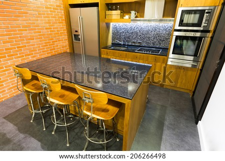 Stylish modern contemporary kitchen with island bar, chair and home appliances - stock photo