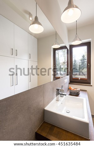 Stylish modern designed bathroom with wooden unit and white sink