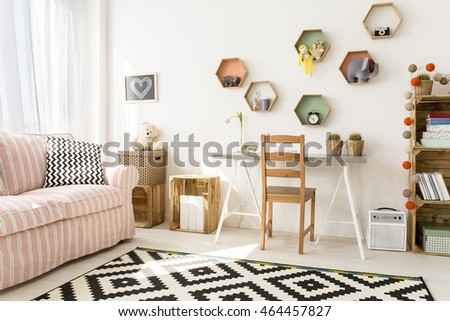 Stylish modern room designed for teenage girl. By the window big sofa in red pattern, next to it study desk