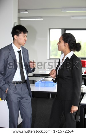 Stylish multiethnic young business man and woman in a discussion standing facing each other in the office as they discuss a problem - stock photo