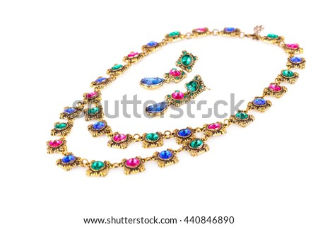 Stylish necklace and earrings with colorful stones isolated on white background.