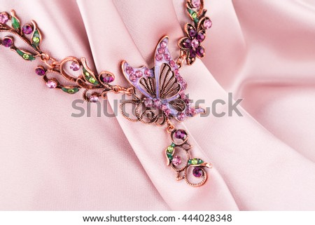 Stylish necklace on pink fabric background.