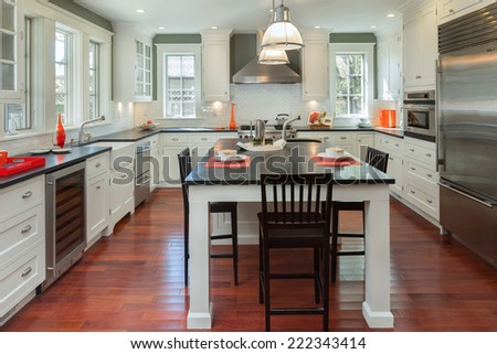 Stylish new kitchen in white with black granite counter tops with stainless steel oven, stove, dual zone wine cooler, coffee machine fridge and Kitchen Island. - stock photo