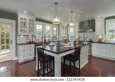 Stylish new kitchen in white with black granite counter tops with stainless steel oven, stove, dual zone wine cooler, coffee machine, fridge and Kitchen Island. - stock photo