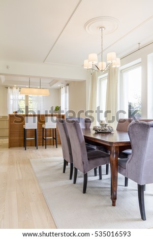 Stylish open room with a massive wooden dining table and chairs