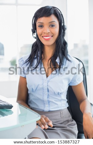 Stylish operator smiling and looking at camera in office
