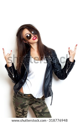 Stylish outfit woman,rock singer,red lips,Stylish fashion blonde sexy young woman with tattoo in a black t-shirt giving the Rock and Roll sign.White background,not isolated.Amazing hairstyle - stock photo