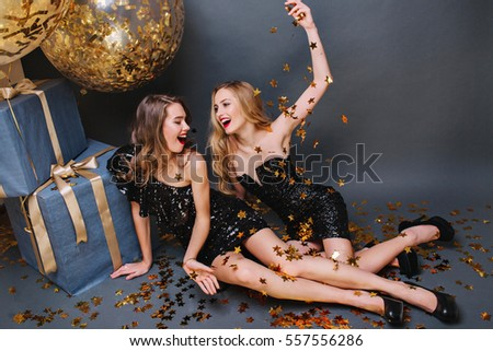 Stylish party image from above two joyful women in luxury black dresses having fun with tinsels on floor on black background. Big balloons, presents, celebrating birthday, expressing positive emotions