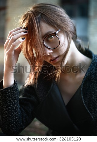 stylish portrait of a beautiful young fashion girl in glasses on a city street - stock photo