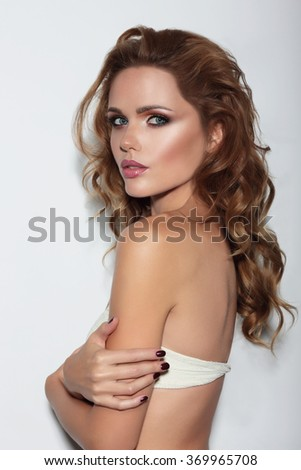 Stylish portrait of a young woman against a white wall. - stock photo