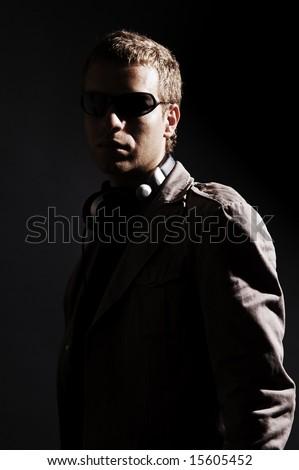 stylish portrait of handsome dj over dark background - stock photo