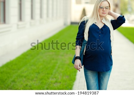 Stylish Pregnancy Concept. Portrait of a fashionable mommy with long blond hair wearing casual trendy clothes and sunglasses and going shopping with blue leather bag. Sunny weather. Outdoor shot