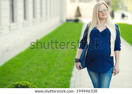 Stylish Pregnancy Concept. Portrait of a fashionable mommy with long blond hair wearing casual trendy clothes, eyewear and going shopping with blue leather bag. Sunny weather. Outdoor shot - stock photo