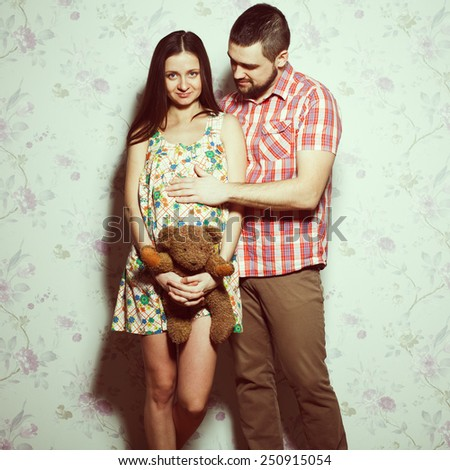 Stylish pregnancy concept: portrait of couple of hipsters (husband and wife) in trendy clothes (shirt, dress, jeans) holding teddy bear and smiling. Vintage (retro) style. Studio shot - stock photo