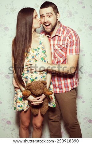 Stylish pregnancy concept: portrait of couple of hipsters (husband and wife) in trendy clothes (shirt, dress, jeans) holding teddy bear and kissing. Vintage (retro) style. Studio shot - stock photo