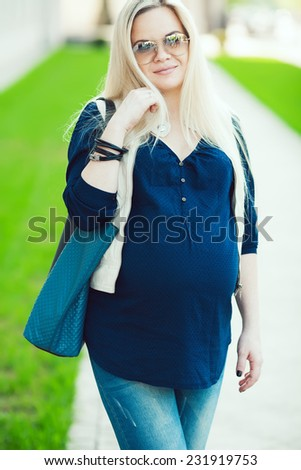 Stylish Pregnancy Concept. Portrait of fashionable mommy with long blond hair wearing casual trendy clothes, eyewear and going shopping with blue leather bag. Sunny weather. Outdoor shot